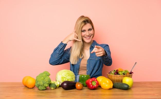Jeune femme blonde avec beaucoup de légumes faisant un geste de téléphone et pointant devant