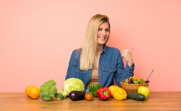 Jeune femme blonde avec beaucoup de légumes pointant sur le côté pour présenter un produit