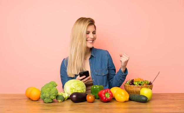 Jeune femme blonde avec beaucoup de légumes avec téléphone en position de victoire