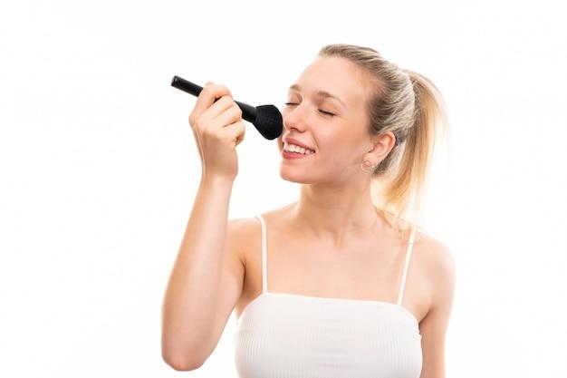 Jeune femme blonde sur blanc isolé avec pinceau de maquillage