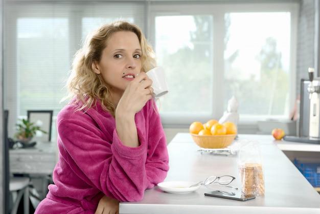 Jeune femme blonde boit du café le matin