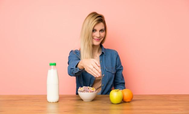 Jeune femme blonde avec bol de céréales poignée de main après bonne affaire