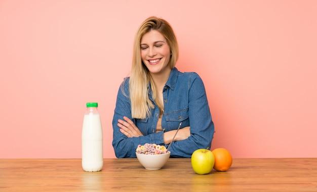 Jeune femme blonde avec un bol de céréales en riant
