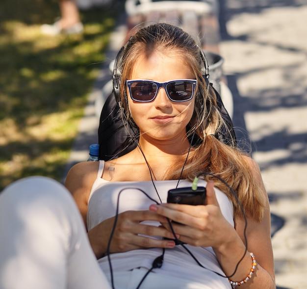 Jeune femme blonde bouclée se trouve, profite de la journée d'été, des blogs et des chats via un téléphone intelligent, porte des nuances à la mode, a un sourire positif, recrée pendant les vacances