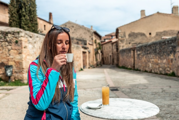 Jeune femme blonde buvant un café sur une terrasse d'un bar dans une vieille ville espagnole.