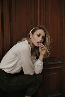 Une jeune femme blonde calme et réfléchie en pantalon de velours foncé et chemisier blanc regarde dans la caméra, s'accroupit près de la porte en bois