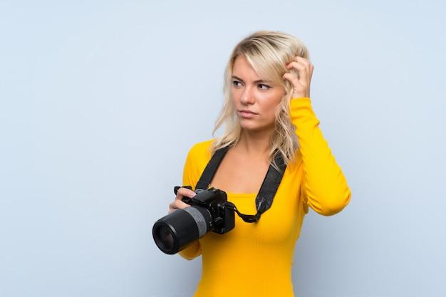 Jeune femme blonde avec une caméra professionnelle et réfléchie