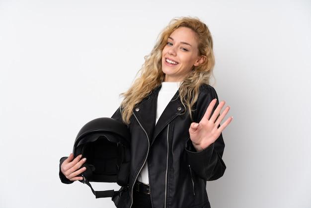 Jeune femme blonde avec un casque de moto isolé sur un mur blanc saluant avec la main avec une expression heureuse