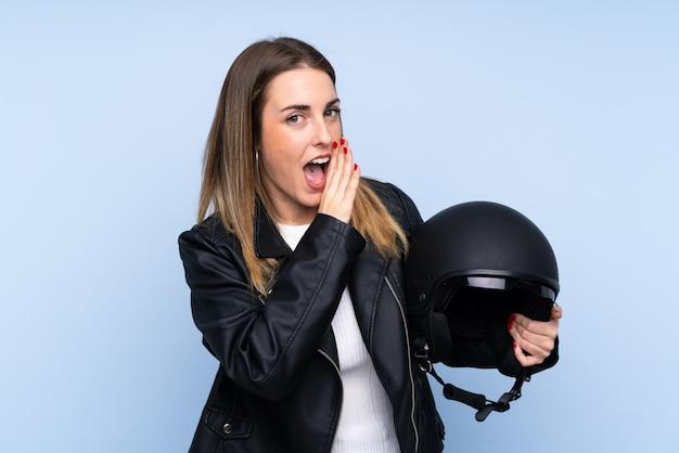 Jeune femme blonde avec un casque de moto sur mur bleu isolé chuchoter quelque chose