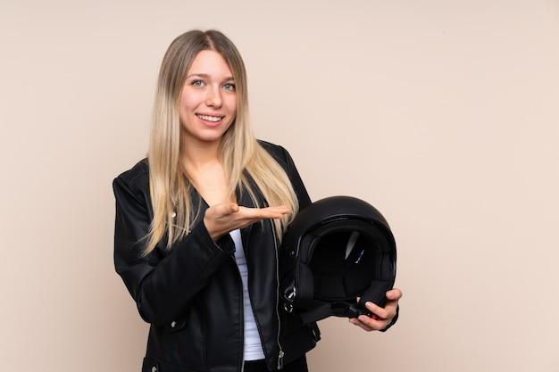 Jeune femme blonde avec un casque de moto sur un mur isolé, tendant les mains sur le côté pour inviter à venir