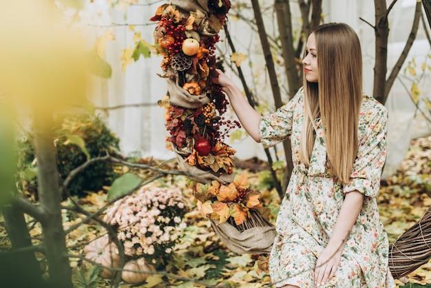 Jeune femme blonde caucasienne dans des vêtements élégants touchant les feuilles à l'extérieur alors qu'elle était assise à la balançoire décorée le jour de l'automne et souriant