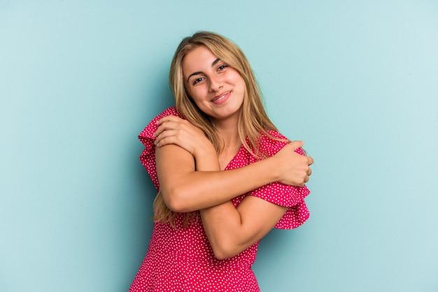 Jeune femme blonde caucasienne isolée sur fond bleu câlins, souriante insouciante et heureuse.