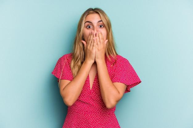 Jeune femme blonde caucasienne isolée sur fond bleu choqué couvrant la bouche avec les mains.