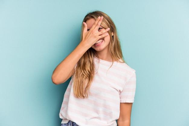 Jeune femme blonde caucasienne isolée sur fond bleu clignote à la caméra à travers les doigts, embarrassé couvrant le visage.