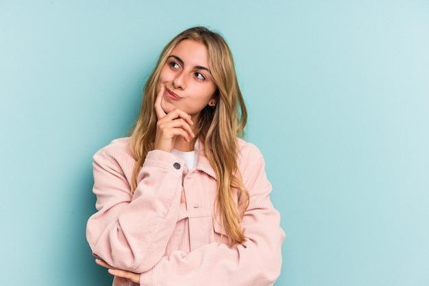 Jeune femme blonde caucasienne isolée sur fond bleu contemplant, planifiant une stratégie, réfléchissant à la manière d'une entreprise.