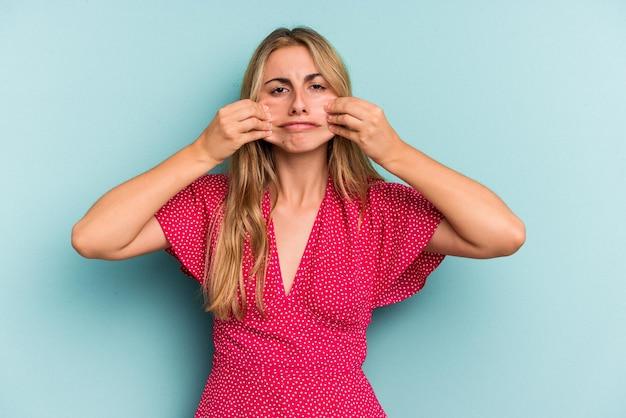 Jeune femme blonde caucasienne isolée sur fond bleu doutant entre deux options.