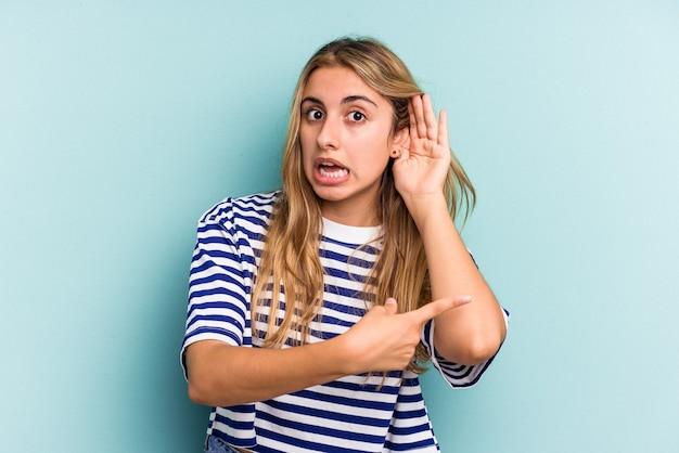 Jeune femme blonde caucasienne isolée sur fond bleu essayant d'écouter un potin.