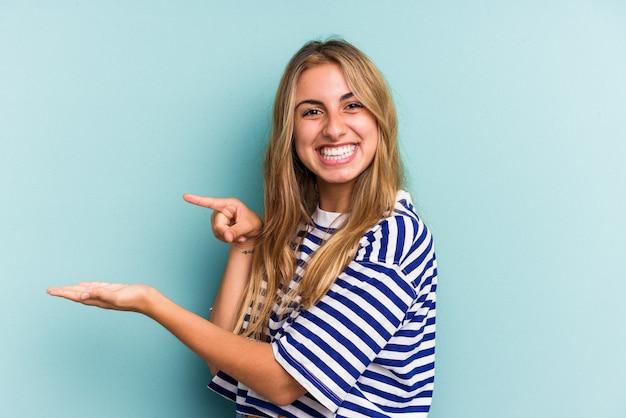 Jeune femme blonde caucasienne isolée sur fond bleu excité tenant un espace de copie sur la paume.