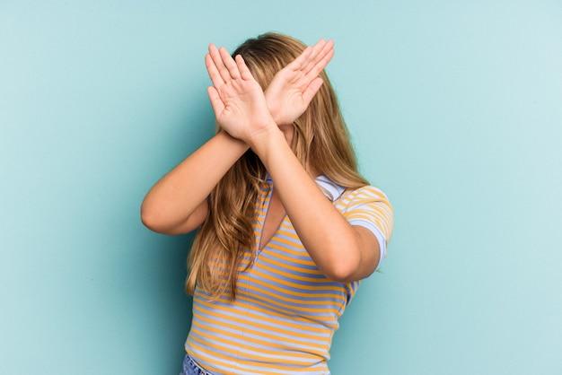 Jeune femme blonde caucasienne isolée sur fond bleu en gardant les deux bras croisés, concept de déni.