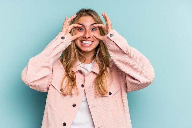 Jeune femme blonde caucasienne isolée sur fond bleu en gardant les yeux ouverts pour trouver une opportunité de réussite.