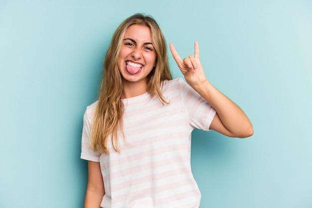 Jeune femme blonde caucasienne isolée sur fond bleu montrant un geste de cornes comme concept de révolution.