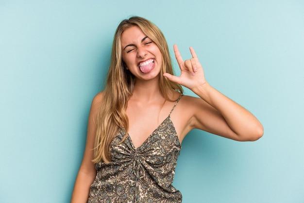Jeune femme blonde caucasienne isolée sur fond bleu montrant un geste rock avec les doigts