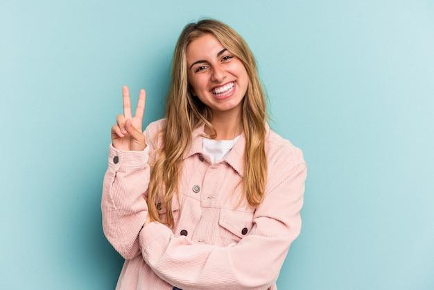 Jeune femme blonde caucasienne isolée sur fond bleu montrant le numéro deux avec les doigts.