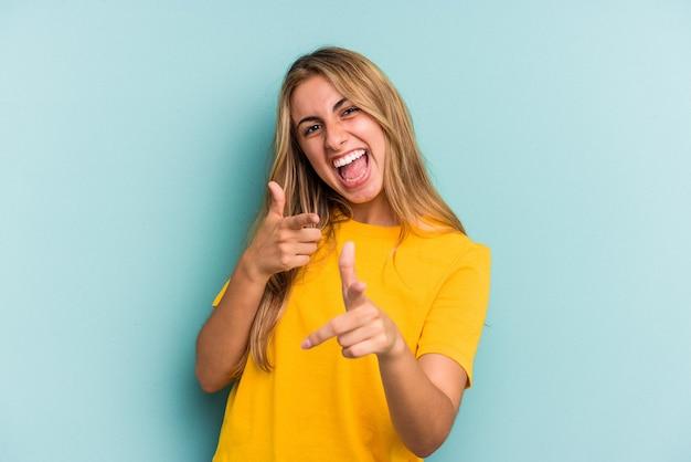 Jeune femme blonde caucasienne isolée sur fond bleu pointant vers l'avant avec les doigts.