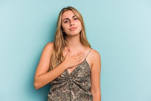 Jeune femme blonde caucasienne isolée sur fond bleu prêtant serment, mettant la main sur la poitrine.