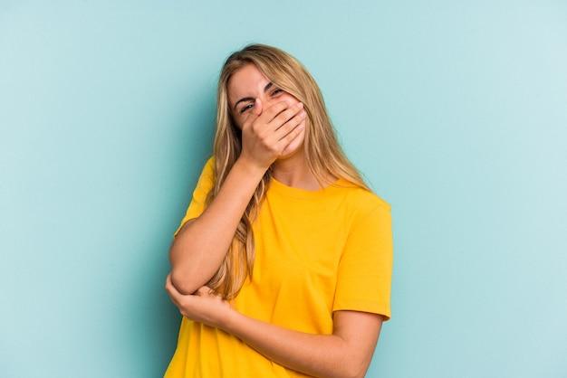 Jeune femme blonde caucasienne isolée sur fond bleu riant émotion heureuse, insouciante et naturelle.