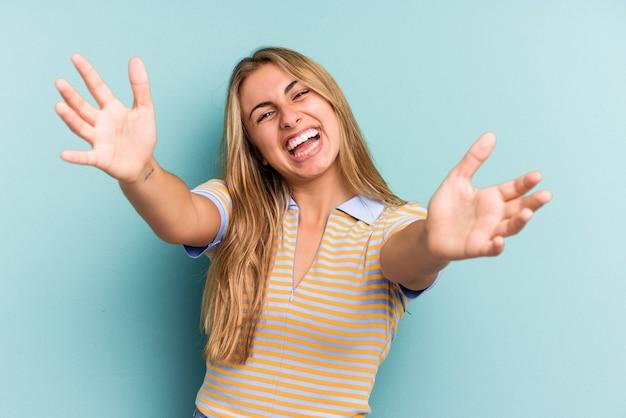 Jeune femme blonde caucasienne isolée sur fond bleu se sent confiante en donnant un câlin à la caméra.