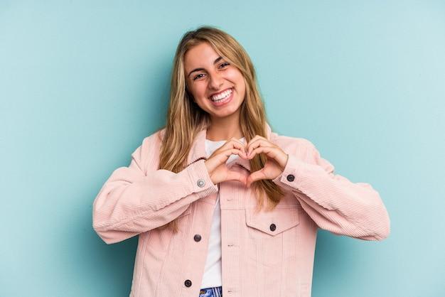 Jeune femme blonde caucasienne isolée sur fond bleu souriant et montrant une forme de coeur avec les mains.