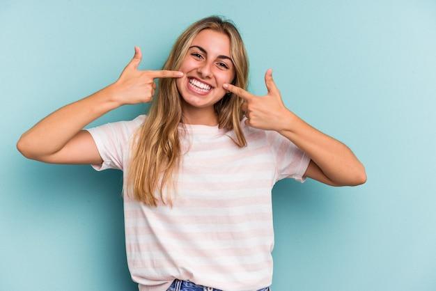 Jeune femme blonde caucasienne isolée sur fond bleu sourit, pointant du doigt la bouche.