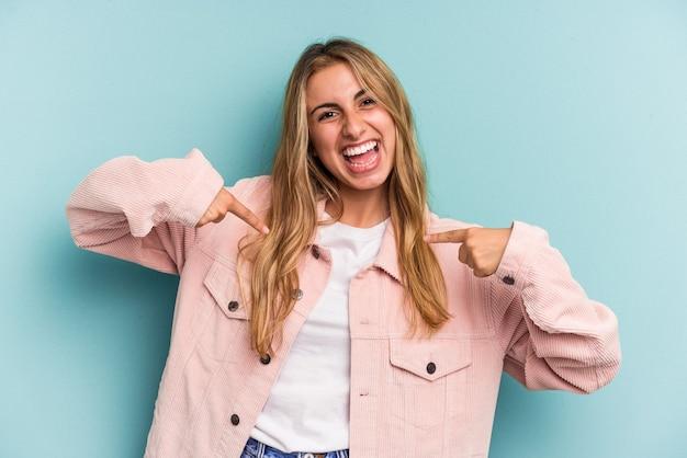 Jeune femme blonde caucasienne isolée sur fond bleu surpris en pointant avec le doigt, souriant largement.
