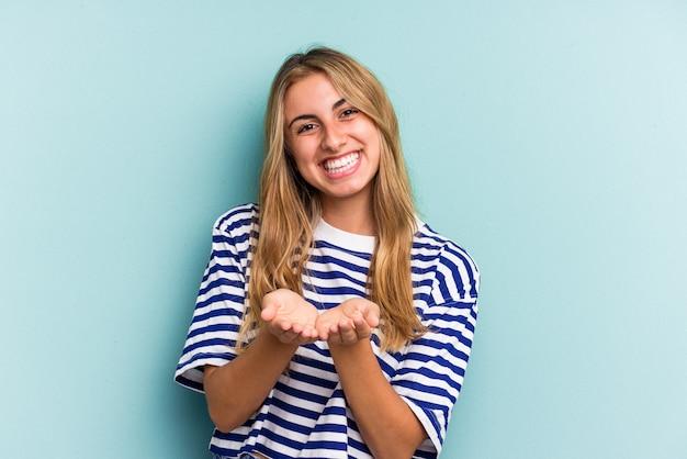 Jeune femme blonde caucasienne isolée sur fond bleu tenant quelque chose avec des paumes, offrant à la caméra.