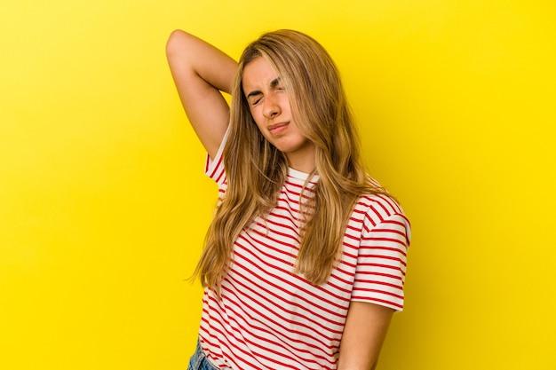 Jeune femme blonde caucasienne isolée sur fond jaune ayant une douleur au cou due au stress, en la massant et en la touchant avec la main.