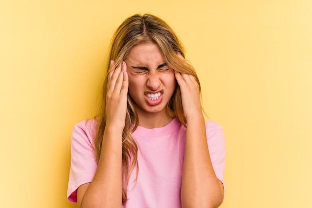 Jeune femme blonde caucasienne isolée sur fond jaune ayant un mal de tête, touchant le devant du visage.