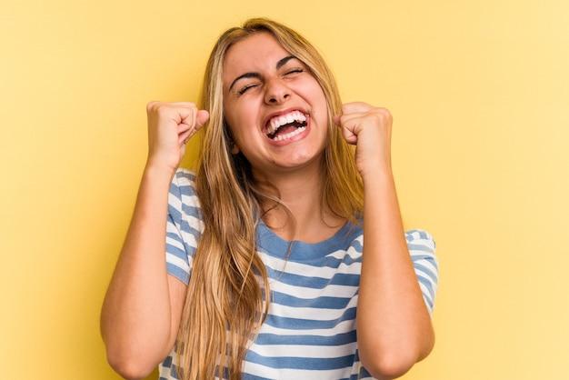 Jeune femme blonde caucasienne isolée sur fond jaune célébrant une victoire, une passion et un enthousiasme, une expression heureuse.