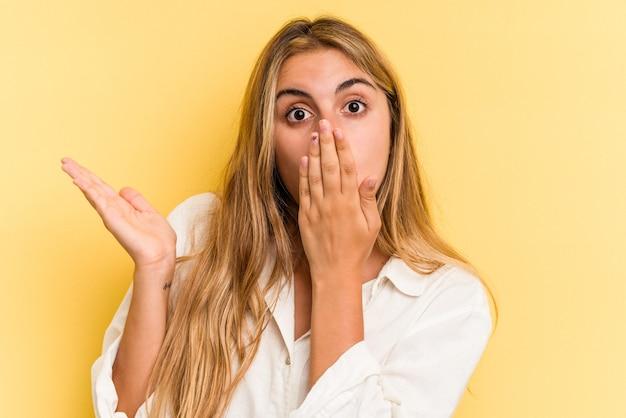 Jeune femme blonde caucasienne isolée sur fond jaune impressionné tenant l'espace de copie sur la paume.