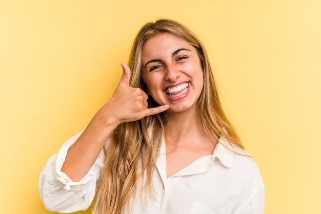 Jeune femme blonde caucasienne isolée sur fond jaune montrant un geste d'appel de téléphone portable avec les doigts.