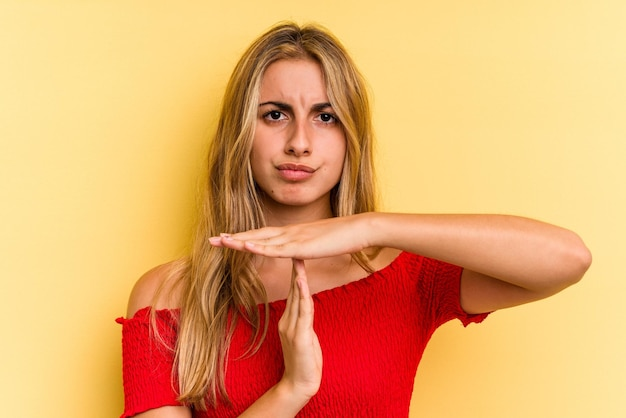 Jeune femme blonde caucasienne isolée sur fond jaune montrant un geste de délai d'attente.