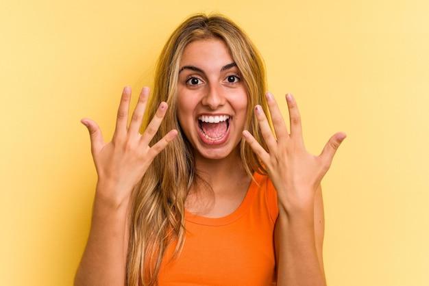 Jeune femme blonde caucasienne isolée sur fond jaune montrant le numéro dix avec les mains.