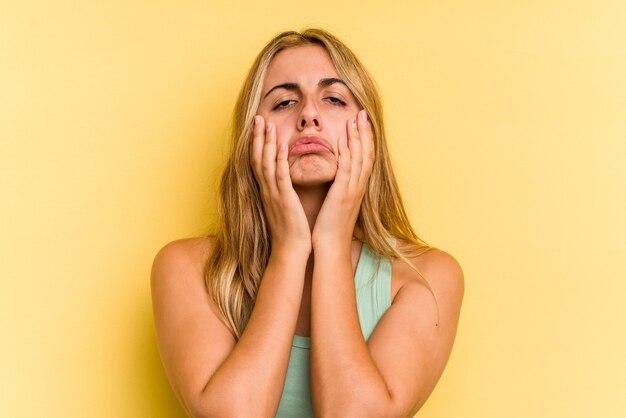 Jeune femme blonde caucasienne isolée sur fond jaune pleurnichant et pleurant de manière inconsolable.