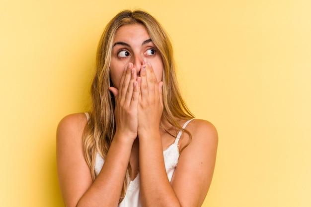 Jeune femme blonde caucasienne isolée sur fond jaune réfléchie à la recherche d'un espace de copie couvrant la bouche avec la main.