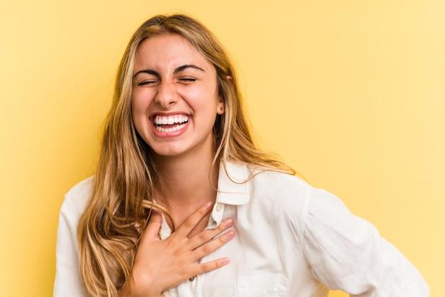 Jeune femme blonde caucasienne isolée sur fond jaune en riant en gardant les mains sur le cœur, concept de bonheur.