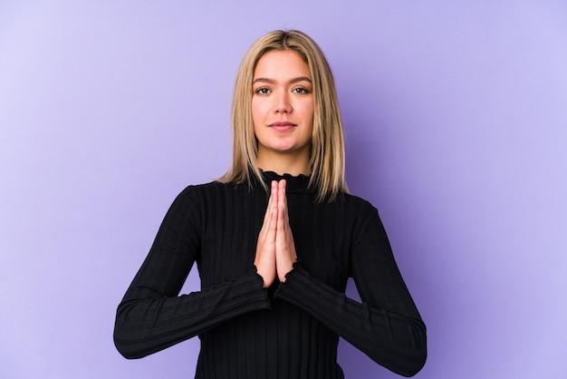 Jeune femme blonde caucasienne isolée priant, montrant la dévotion, personne religieuse à la recherche d'inspiration divine.