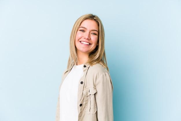 Jeune femme blonde caucasienne isolée regarde de côté souriant, gai et agréable.