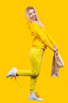 Jeune femme blonde caucasienne joyeuse avec des sacs en papier écologique en costume sportif jaune, isolé
