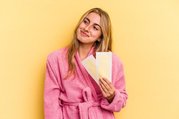 Jeune femme blonde caucasienne portant un peignoir tenant des bandes dépilatoires isolées sur fond jaune rêvant d'atteindre des objectifs et des objectifs