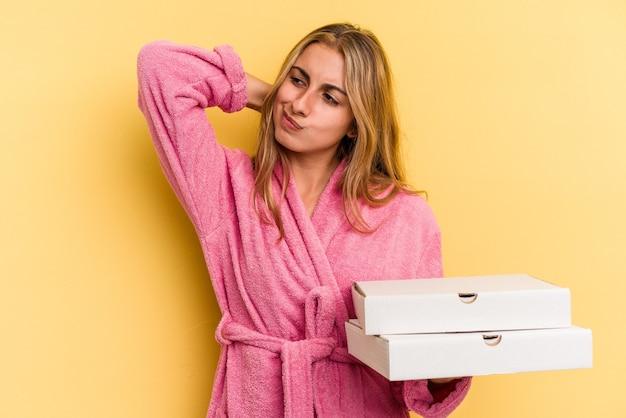 Jeune femme blonde caucasienne portant un peignoir tenant des pizzas isolées sur fond jaune touchant l'arrière de la tête, pensant et faisant un choix.